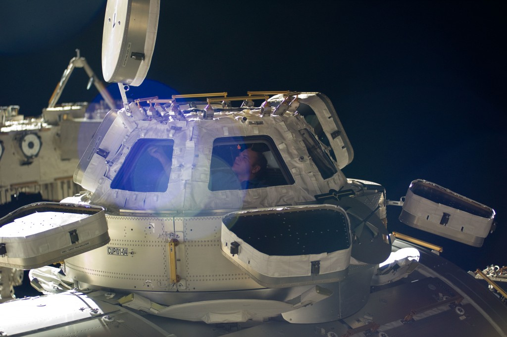 Russian cosmonaut Oleg Kotov, Expedition 23 commander, is pictured in a window of the Cupola of the International Space Station on 9 May 2010 (NASA)
